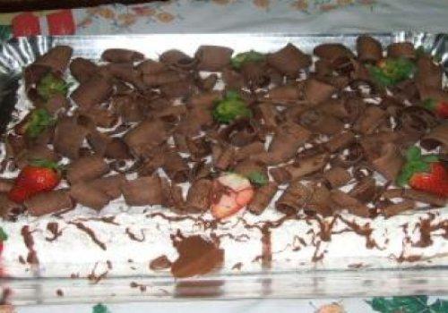 Bolo de chocolate com recheio de flocos e creme com morangos